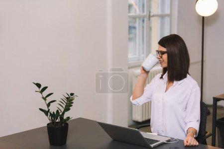 Photo pour Douce brune travaillant au bureau. Fille avec des lunettes boire du café ou du thé . - image libre de droit