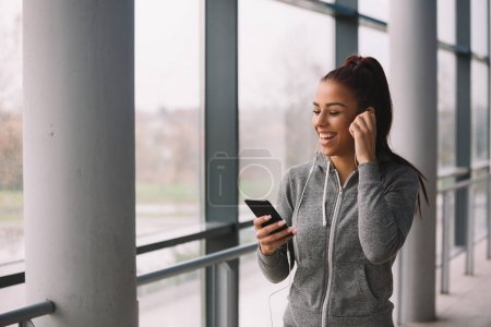 Sporty girl listening to music on smart phone.