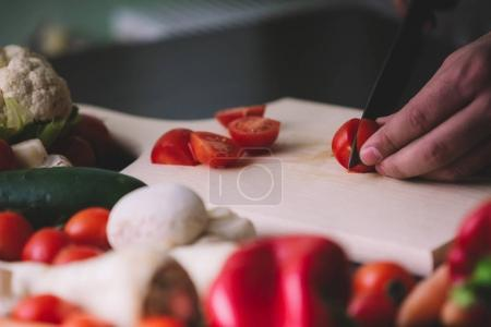 Close-up of man hands while cutting cherry tomatoes on wooden board.