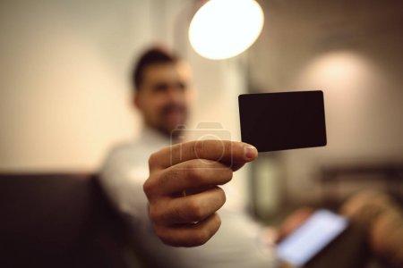 Hand holding blank black credit card mockup front side view. Plastic bank-card design mock up