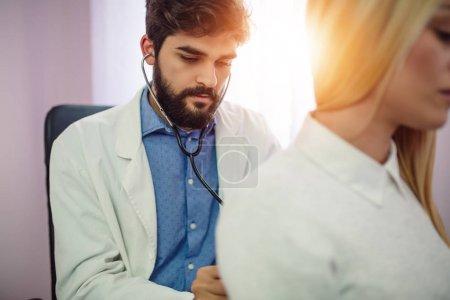 Médecin examinant le patient avec stéthoscope au cabinet médical. Médecin utilisant le stéthoscope pour examiner le c?ur du patient. Portrait de beau médecin masculin examine un patient avec stéthoscope .