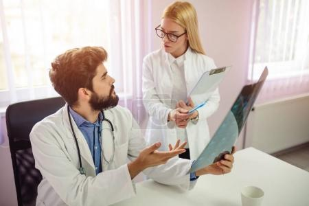 Male and female doctor having discussion in hospital. Doctors analyze x-ray.