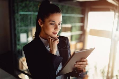 Portrait of modern businesswoman in formal wear with ponytail using tablet.