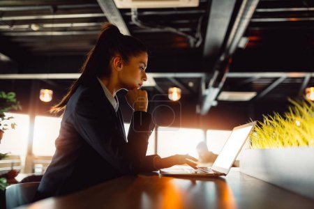 Photo for Side view of an attractive girl while using laptop computer. - Royalty Free Image