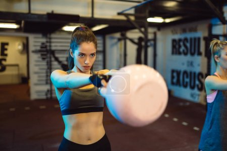 Fitness woman doing a weight training by lifting kettlebell. Muscular fitness woman, holds up a pink kettlebell crossfit the gym. Fitness woman in the gym. Crossfit woman. Crossfit and fitness