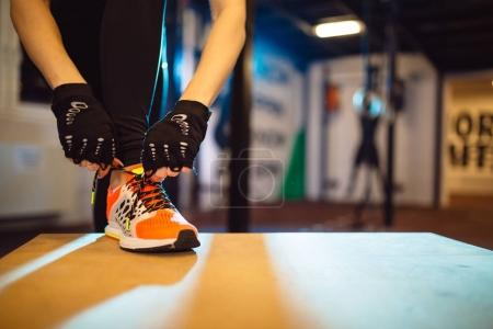 Close-up of female hands while preparing for workout. Woman tying a shoelace and preparing for fitness.