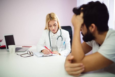 Photo for Female doctor filling patient form. Male patient with problem talking with doctor. - Royalty Free Image