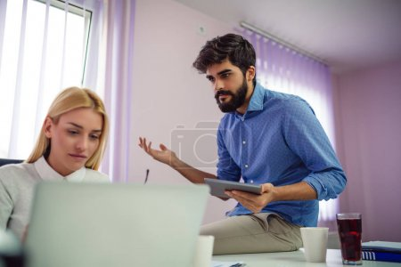 Young businessman and woman working together in office with laptop and mobile