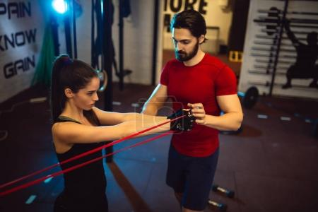 Young woman exercising at gym with male personal trainer.