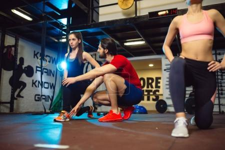 Young women exercising at gym with male personal trainer.