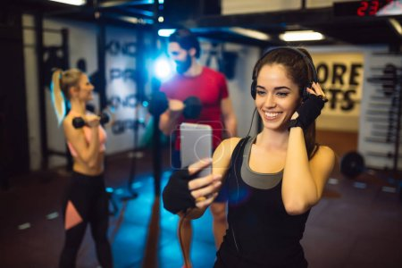 Photo for Young woman taking selfie during workout in gym - Royalty Free Image