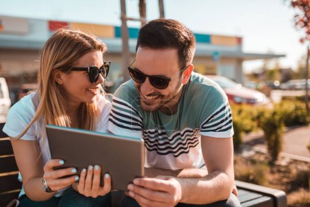Young couple with sunglasses is sitting outside on a bench and using tablet