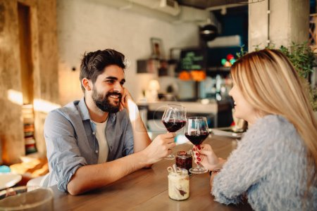 Cheers! Young handsome man is drinking wine with his girlfriend in cafe