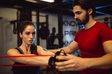 Personal trainer motivated to show to trainee how to get maximum from exercise