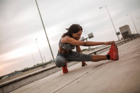 African american girl is stretching leg in the street after running