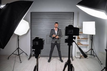 Photo pour Vidéo du programme de formation d'un jeune coach d'affaires. Becxtage de l'enregistrement d'une vidéo de la conférence d'un homme d'affaires. Enregistrer une émission de télévision avec un jeune beau présentateur masculin . - image libre de droit