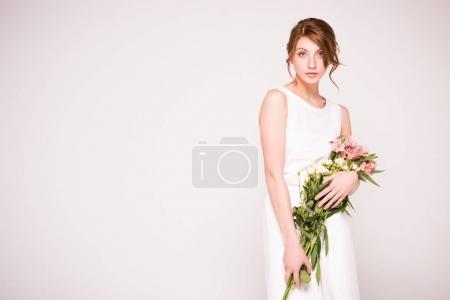 Photo pour Fille en robe blanche tenant belle floraison fleurs et regardant la caméra isolée sur fond gris - image libre de droit