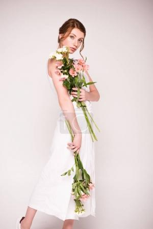 Photo for Gorgeous girl in white dress holding tender flowers and looking at camera isolated on grey - Royalty Free Image