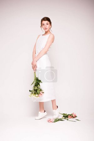Photo for Attractive young woman in white dress holding beautiful flowers and looking at camera isolated on grey - Royalty Free Image