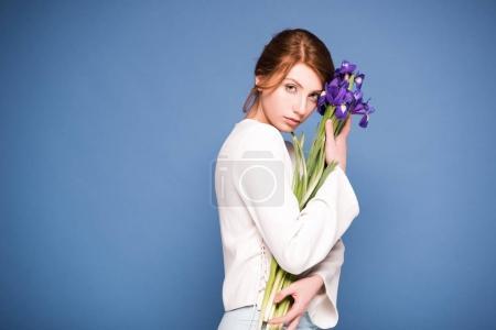 Photo pour Belle jeune femme holding iris fleurs et regardant la caméra isolée sur bleu - image libre de droit