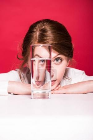 Photo for Young woman looking at camera through glass of water isolated on red - Royalty Free Image