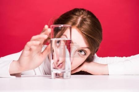 Photo pour Vue rapprochée des maux jeune femme regardant de verre d'eau isolée sur rouge - image libre de droit