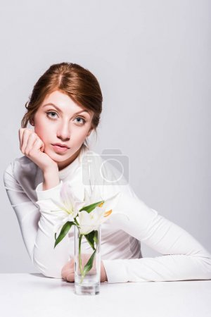 Photo for Gorgeous young woman with tender lily flowers looking at camera isolated on grey - Royalty Free Image