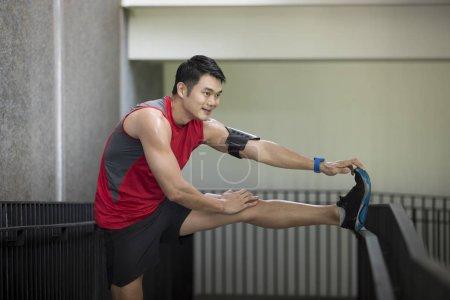 Asian man stretching during exercising