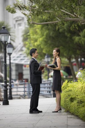 Photo for Two Asian Business colleagues talking outside in modern Asian city. - Royalty Free Image
