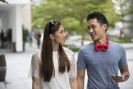 Asian couple walking down street