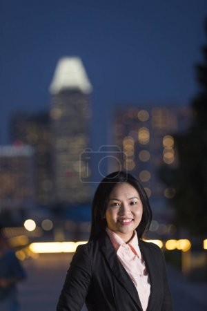 Asian businesswoman in city at night