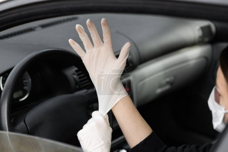 Photo for Woman in protective medical mask is wearing rubber gloves for protect himself from bacteria virus while planning to drive. Protective mask while quarantine, pandemic, covid 19, coronavirus, infection - Royalty Free Image