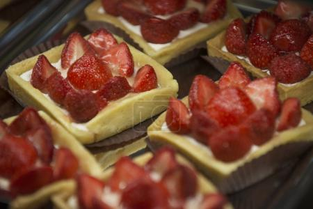 Close up of fresh cakes with strawberries in confectionery department