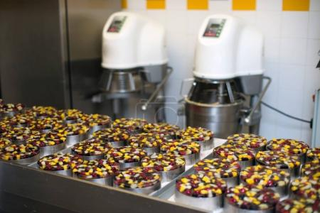 Photo for Dozens biscuit cakes with fruits under jello with kitchen equipment on background - Royalty Free Image