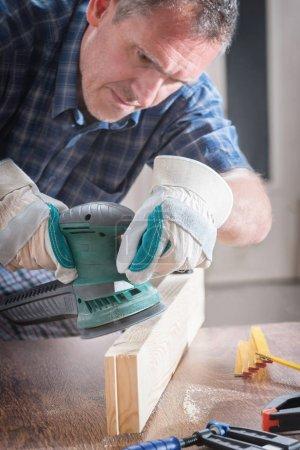 Man sanding a wood with orbital sander