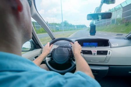 Photo pour Conduite d'une voiture - vue du siège arrière. Mains sur le volant - image libre de droit
