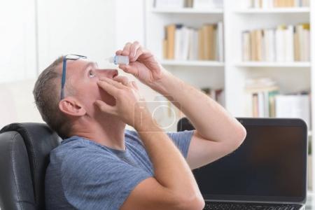 Photo pour Application de gouttes pour les yeux après une longue séance à l'ordinateur l'homme - image libre de droit