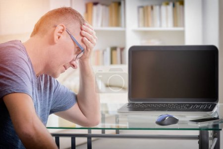 Freelancer man at workplace in office holding his head on hands