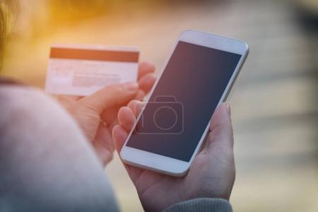 Photo for Hands holding credit card and using smart phone outdoor, mobile online payment concept - Royalty Free Image