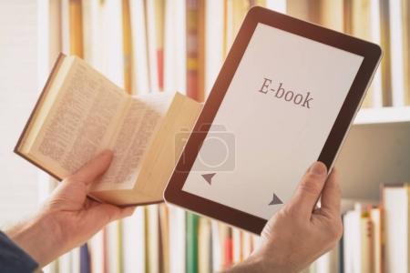 Man holding a modern ebook reader and book