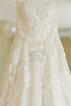 Photo pour Robe de mariée accrochée au miroir, matinée de la mariée - image libre de droit