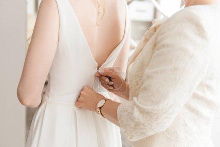 Photo pour Femme zippant robe de mariée, plan recadré - image libre de droit