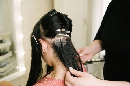 Photo pour Le coiffeur fait des extensions de cheveux à une jeune fille dans un salon de beauté. Soins capillaires professionnels . - image libre de droit