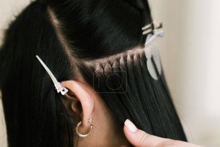 Photo pour Le coiffeur fait des extensions de cheveux à une jeune fille dans un salon de beauté. Soins capillaires professionnels. Gros plan des capsules et des mèches de cheveux adultes - image libre de droit
