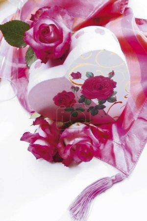 herzförmige Geschenkschachtel mit Rosen auf seidigem Tuch