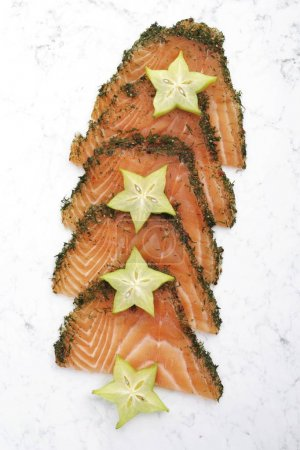 Sliced salmon (gravlax) garnished with starfruit