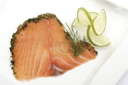 Sliced salmon (gravlax) garnished with lime slices and dill