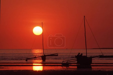 Beautiful red sunset and sea with boats and people...