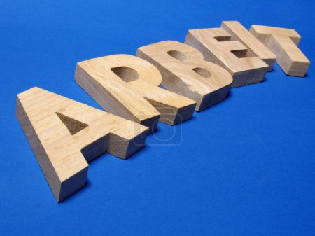 Alphabet wooden letters on blue surface,  German word of work, job