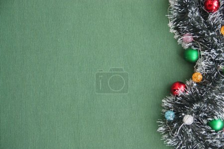 Photo for New Year's tinsel, garland, balls on a green background. Place for the inscription. New Year and Christmas background for congratulations, cards, advertising, posters and banners, magazines and newspapers. - Royalty Free Image